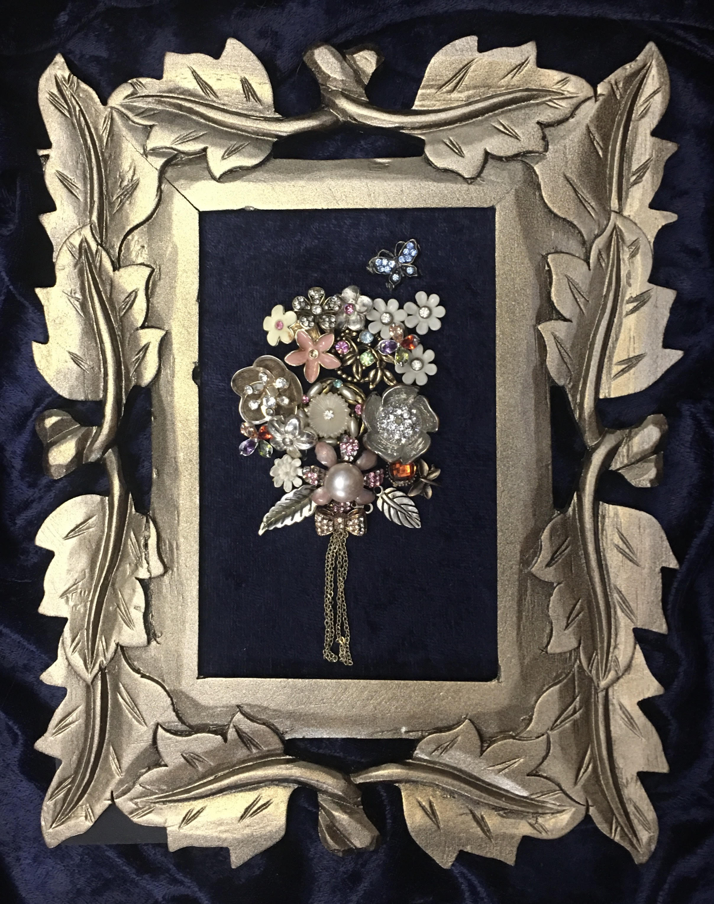 Frame with jewelry laid out on it.